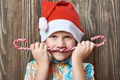 Μικρό παιδί στην κόκκινη ΚΑΠ με τον κάλαμο καραμελών Χριστουγέννων δύο Στοκ Εικόνες