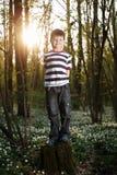 Μικρό παιδί στο δάσος στον τομέα λουλουδιών Στοκ εικόνα με δικαίωμα ελεύθερης χρήσης
