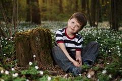 Μικρό παιδί στο δάσος στον τομέα λουλουδιών Στοκ Φωτογραφίες