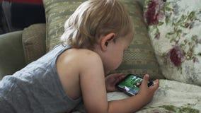Μικρό παιδί στο βίντεο προσοχής καναπέδων στο smartphone Παιδική ηλικία συσκευή διασκεδάσεις απόθεμα βίντεο