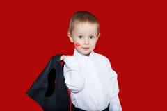 Μικρό παιδί στο επιχειρησιακό κοστούμι με το ίχνος φιλιών στο μάγουλο με στοκ εικόνες