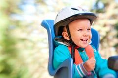 Μικρό παιδί στο κάθισμα παιδιών ποδηλάτων ευτυχές Στοκ φωτογραφία με δικαίωμα ελεύθερης χρήσης
