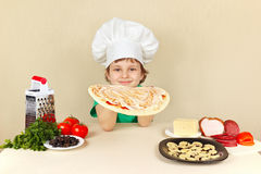 Μικρό παιδί στο καπέλο αρχιμαγείρων που λερώνεται με τη σάλτσα στην κρούστα πιτσών Στοκ Φωτογραφία