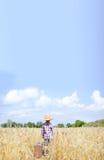 Μικρό παιδί στο καπέλο αχύρου που στέκεται εκτός από τη βαλίτσα Στοκ φωτογραφία με δικαίωμα ελεύθερης χρήσης