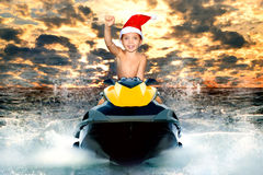 Μικρό παιδί στο καπέλο Santa που οδηγά ένα μηχανικό δίκυκλο νερού στα κύματα Στοκ εικόνες με δικαίωμα ελεύθερης χρήσης