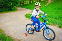 Μικρό παιδί στο ποδήλατο στο πράσινο πάρκο υπαίθριο το καλοκαίρι στοκ εικόνες με δικαίωμα ελεύθερης χρήσης