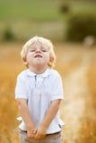 Μικρό παιδί τριών ετών που έχουν τη διασκέδαση στον κίτρινο τομέα σανού Στοκ Εικόνες