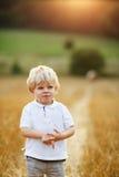 Μικρό παιδί τριών ετών που έχουν τη διασκέδαση στον κίτρινο τομέα σανού Στοκ Φωτογραφία