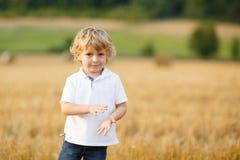 Μικρό παιδί τριών ετών που έχουν τη διασκέδαση στον κίτρινο τομέα σανού Στοκ φωτογραφίες με δικαίωμα ελεύθερης χρήσης