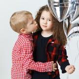 Μικρό παιδί congatulate λίγο σγουρό κορίτσι, φιλί, μπαλόνια στούντιο Καθιερώνοντα τη μόδα ενδύματα μόδας Στοκ Φωτογραφίες