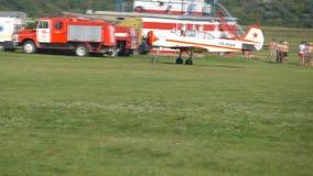 Μικρό παλαιό αεροπλάνο προωστήρων που οδηγά στην πράσινη χλόη στον αερολιμένα Κλείστε επάνω του μικρού αεροπλάνου προετοιμαμένος  απόθεμα βίντεο