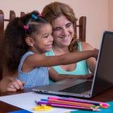 Μικρό πολυφυλετικό κορίτσι και η μητέρα της που εργάζονται σε ένα lap-top comput Στοκ Εικόνες