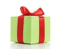 Μικρό πράσινο κιβώτιο δώρων το κόκκινο τόξο κορδελλών που απομονώνεται με στο λευκό Στοκ Εικόνα