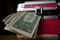 Μικρό ρόδινο strongbox με τις ασημένιες άκρες που κρατούν το παχύ πακέτο των χρημάτων (αμερικανικά δολάρια, Δολ ΗΠΑ) στοκ εικόνα
