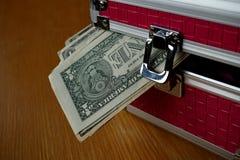 Μικρό ρόδινο strongbox με τις ασημένιες άκρες που κρατούν το παχύ πακέτο των χρημάτων (αμερικανικά δολάρια, Δολ ΗΠΑ) στοκ φωτογραφίες