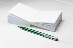 μικρό σημειωματάριο στο άσπρο γραφείο Στοκ Εικόνα