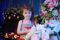 Μικρό σκοτεινός-μαλλιαρό κορίτσι σε ένα κόκκινο φόρεμα δίπλα στα λουλούδια σε ένα βάζο στοκ φωτογραφία