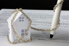 μικρό σπίτι εγγράφου που δένεται με την αλυσίδα Στοκ εικόνα με δικαίωμα ελεύθερης χρήσης