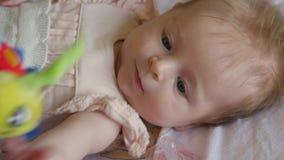 Μικρό χαμογελώντας μωρό με ένα παιχνίδι Ευτυχές παιχνίδι μωρών με την ένωση του παιχνιδιού απόθεμα βίντεο
