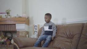 Μικρό χαριτωμένο αγόρι παιδιών αφροαμερικάνων που πηδά στον καναπέ στο υπόβαθρο του άνετου καθιστικού Σχέση mom και γιος ? φιλμ μικρού μήκους