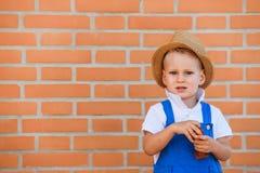 Μικρό χαριτωμένο ξανθό αγόρι στο καπέλο και συνολικά στοκ φωτογραφίες με δικαίωμα ελεύθερης χρήσης