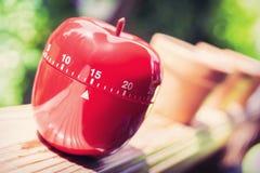 15 μικρό χρονόμετρο αυγών κουζινών στη μορφή της Apple που στέκεται σε ένα κιγκλίδωμα Στοκ Εικόνες
