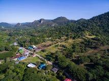 Μικρό χωριό στην κοιλάδα με το δάσος, το βουνό, και το μπλε ουρανό στοκ φωτογραφία