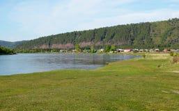 Μικρό χωριό στην όχθη ποταμού γραφικό καλοκαίρι λιβαδιού τοπίων αγελάδων Στοκ Φωτογραφίες