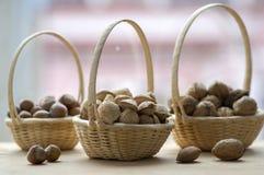 Μικρό ψάθινο καλάθι τρία με τα αμύγδαλα, τα ξύλα καρυδιάς και τα φουντούκια στοκ φωτογραφίες με δικαίωμα ελεύθερης χρήσης