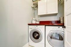 Μικρό δωμάτιο πλυντηρίων με το πάτωμα κεραμιδιών, την πόρτα, και το στεγνωτήρα πλυσίματος Στοκ εικόνες με δικαίωμα ελεύθερης χρήσης