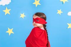 Μικρό superhero παιδικών παιχνιδιών Παιδί στο υπόβαθρο του φωτεινού μπλε τοίχου με τα άσπρα σύννεφα και τα αστέρια Έννοια δύναμης Στοκ Φωτογραφία