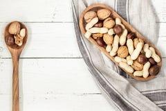 Μικτά καρύδια: ξύλο καρυδιάς, κάστανο, φυστίκι στο ξύλινο κύπελλο στο λευκό Στοκ εικόνες με δικαίωμα ελεύθερης χρήσης