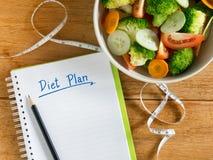 Μικτά κύπελλο σαλάτας λαχανικών και σημειωματάριο σχεδίων διατροφής Στοκ Φωτογραφία