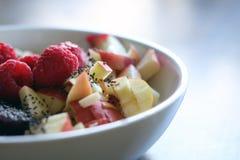 Μικτά φρούτα και δημητριακά σε ένα άσπρο κύπελλο στον καφετή ξύλινο πίνακα Στοκ Εικόνες