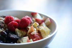 Μικτά φρούτα και δημητριακά σε ένα άσπρο κύπελλο στον καφετή ξύλινο πίνακα Στοκ Φωτογραφίες