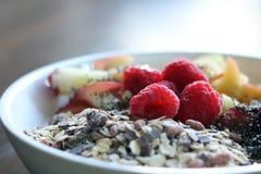 Μικτά φρούτα και δημητριακά σε ένα άσπρο κύπελλο στον καφετή ξύλινο πίνακα Στοκ Φωτογραφία