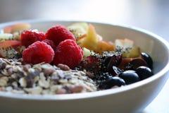 Μικτά φρούτα και δημητριακά σε ένα άσπρο κύπελλο στον καφετή ξύλινο πίνακα Στοκ Εικόνα