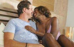 Μικτή ερωτευμένη αγκαλιά ζευγών έθνους μαζί στο σπίτι στο κρεβάτι με την όμορφη εύθυμη αμερικανική γυναίκα μαύρων Αφρικανών και κ στοκ εικόνες