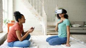 Μικτή συναγωνισμένη γυναίκα που χρησιμοποιεί τα γυαλιά εικονικής πραγματικότητας ενώ ο φίλος της που κρατά τον ψηφιακό υπολογιστή Στοκ Εικόνα