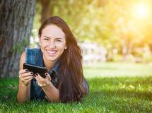 Μικτή φυλή νέο θηλυκό Texting στο τηλέφωνο κυττάρων έξω στο Gra Στοκ φωτογραφία με δικαίωμα ελεύθερης χρήσης