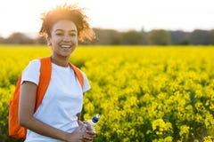 Μικτός έφηβος κοριτσιών αφροαμερικάνων φυλών στα κίτρινα λουλούδια στο S στοκ φωτογραφία