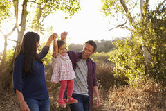 Μικτός περίπατος ζευγών φυλών στην αγροτική πορεία που ανυψώνει τη νέα κόρη στοκ φωτογραφία με δικαίωμα ελεύθερης χρήσης