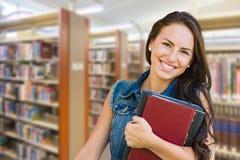 Μικτός σπουδαστής νέων κοριτσιών φυλών με τα σχολικά βιβλία μέσα στη βιβλιοθήκη Στοκ εικόνα με δικαίωμα ελεύθερης χρήσης