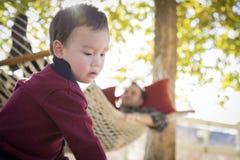 Μικτό αγόρι φυλών που έχει τη διασκέδαση ενώ ρολόγια γονέα από πίσω Στοκ Φωτογραφίες