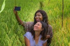 Μικτό ασιατικό κινεζικό κορίτσι έθνους και αμερικανική γυναίκα μαύρων Αφρικανών που παίρνει τις φίλες selfie με το κινητό τηλέφων στοκ φωτογραφία