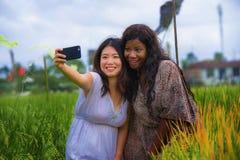 Μικτό ασιατικό κινεζικό κορίτσι έθνους και αμερικανική γυναίκα μαύρων Αφρικανών που παίρνει τις φίλες selfie με το κινητό τηλέφων στοκ εικόνες