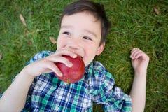 Μικτό κινεζικό και καυκάσιο νέο αγόρι φυλών με τη Apple που χαλαρώνει το Ο Στοκ Εικόνα