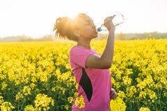 Μικτό πόσιμο νερό δρομέων εφήβων κοριτσιών αφροαμερικάνων φυλών Στοκ εικόνα με δικαίωμα ελεύθερης χρήσης