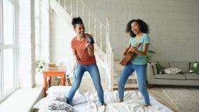 Μικτό τραγούδι χορού κοριτσιών φυλών νέο αστείο με την ακουστική κιθάρα hairdryer και παιχνιδιού σε ένα κρεβάτι διασκέδαση που έχ Στοκ εικόνες με δικαίωμα ελεύθερης χρήσης