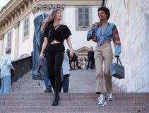 ΜΙΛΑΝΟ, ΙΤΑΛΙΑ - 15 ΙΟΥΝΊΟΥ 2018: Μοντέρνες γυναίκες στα σκαλοπάτια Arengario μετά από τη επίδειξη μόδας ΑΛΜΠΕΡΤΑ FERRETTI στοκ φωτογραφία
